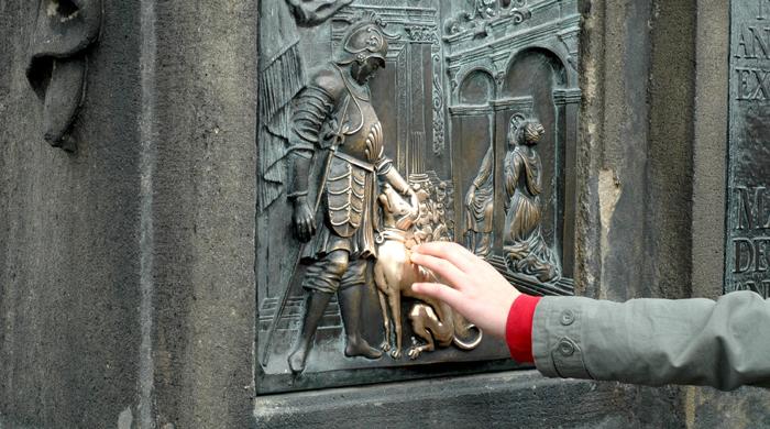 Someone touching St. John of Nepomuk's statue on Prague's Charles Bridge which is held to bring good fortune, Photo @ Paul van Dijk